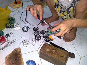 Worker making motorbikes using recycled tin cans