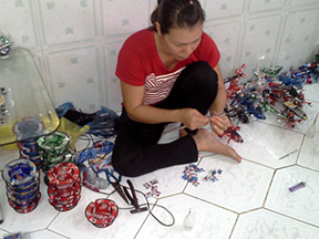 Worker making ashtrays using recycled tin cans