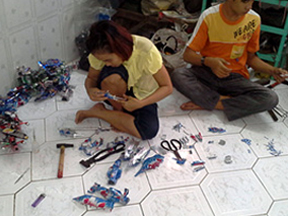 Workers making formula 1 car models using old tin cans